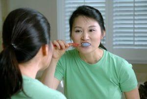 woman brushing her teeth in the mirror