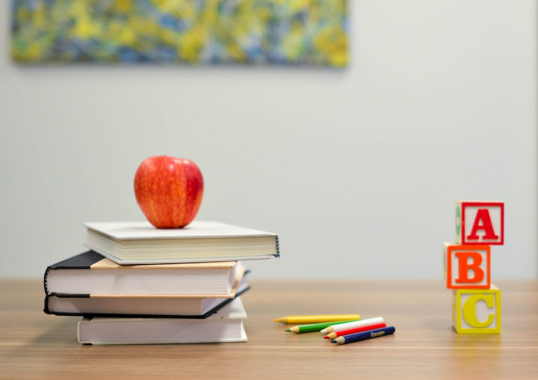 Apple resting on books beside coloring pencils and alphabet blocks