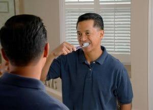 man brushing teeth in the mirror