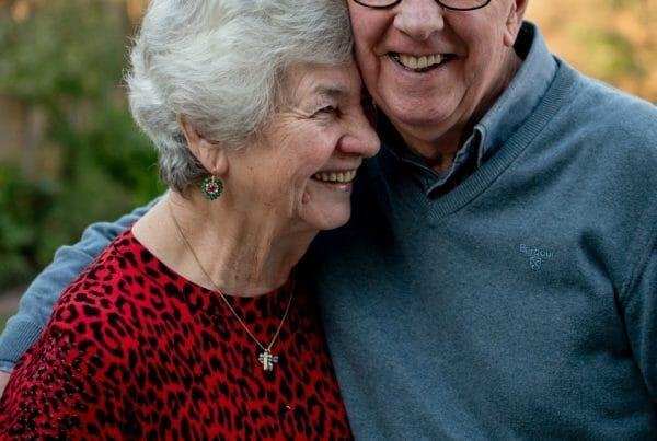 Smiling senior couple dentures vs. dental implants